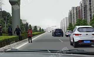 在中央有隔离带的道路上行驶,遇行人试图横穿道路时(如图所示),教练员应及时提示学员___。